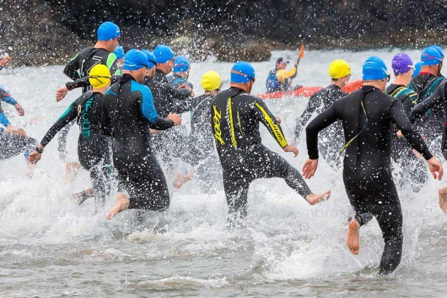 Triathlon competitors enter the water at broad haven